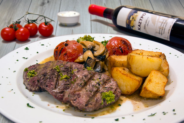 Kastro Oia Restaurant Santorini. Beef fillets on the grill with fresh mushrooms marinated in lime and garnished with baked potatoes and grilled tomatoes.