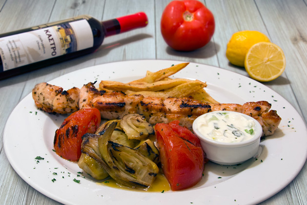 Kastro Oia Restaurant Santorini. Chicken Souvlaki with fries, grilled tomato and yoghurt sauce.